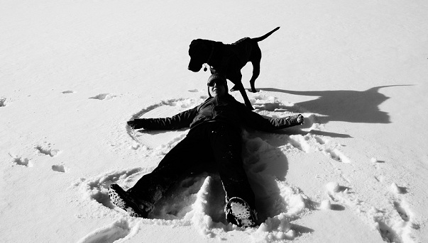 Woman and dog making snow angels!