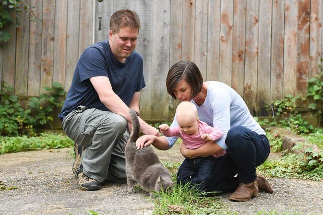 Baby petting the barn cat